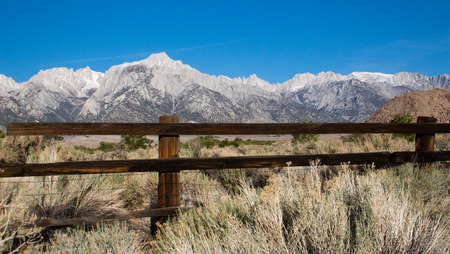 An old fence with the Sierra Nevada mountain range including Mt. Whitney in the background