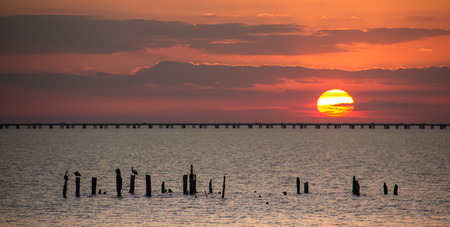 The sun setting behind the causeway over Lake Ponchartrain Stock Photo