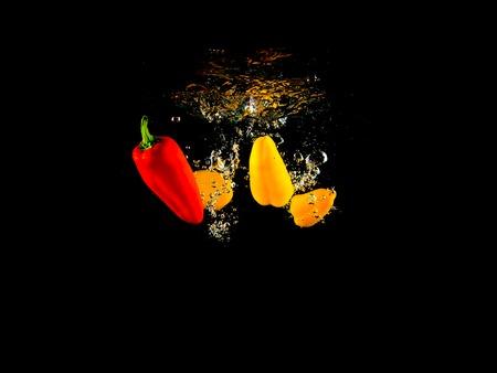 briskness: Dropping Vegetables black background Stock Photo