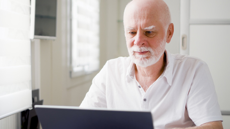 Handsome elderly senior man working on laptop computer at home. Remote freelance work on retirement, active modern lifestyle of older people