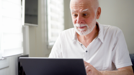 Handsome elderly senior man working on laptop computer at home. Surprized by the news. Remote freelance work on retirement, active modern lifestyle of older people.