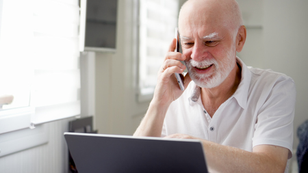 Good-looking handsome senior man sitting at home with laptop and smartphone. Using cellphone discussing project on screen. Remote freelance work on retirement, active modern lifestyle of older people