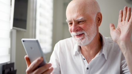 Senior man sitting at home with smartphone. Using mobile talking via messenger app Skype. Smiling waving hand in greeting. Remote freelance work on retirement, active modern lifestyle of older people Banque d'images
