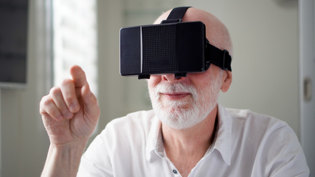 Good-looking handsome senior man in white using VR 360 glasses at home. Making browse and tap gestures. Concept of active modern elderly people, learning to use contemporary technologies.