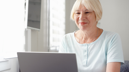Elderly senior blond woman working on laptop computer at home. Received good news excited and happy. Remote freelance work on retirement, active modern lifestyle of older people. Banque d'images