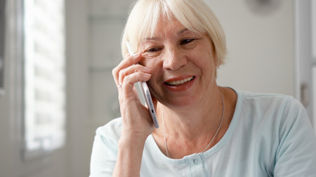 Good-looking blond senior woman sitting at home using smartphone. Retired woman talking on cellphone. Active modern elderly people concept Banque d'images