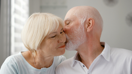 Portrait of happy senior couple at home. Senior man expresses his emotions and kisses his wife. Very emotional moment. Happy family enjoying time together.