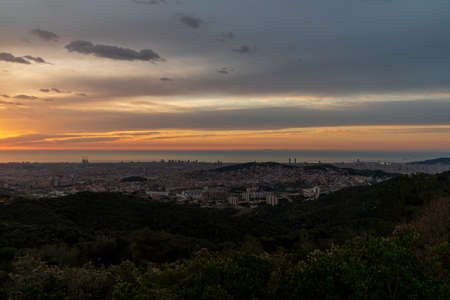 Sunrise on a spring day in the city of Barcelona. We can see the sky, with some clouds that light up like fire, with the sunlight. The water of the Mediterranean Sea, completely flat.