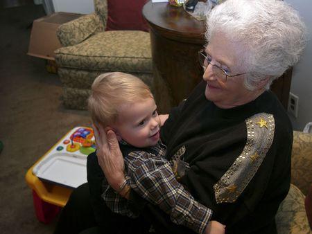 great grandmother: Un gran Ggrandmother que se sienta en una silla que sostiene a su gran nieto