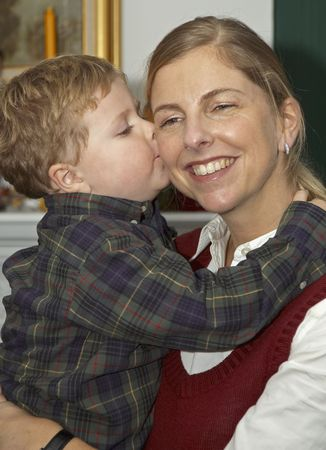 A young boy kissing and hugging his Mother