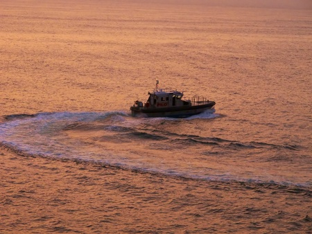 A Pilot Boat manuvering in the water at Sunrise in Bermuda 06/11 Stock Photo - 10004720