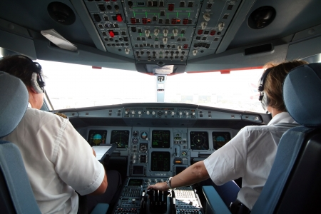 Jet airplane cockpit with two pilots crewmembers Stock Photo