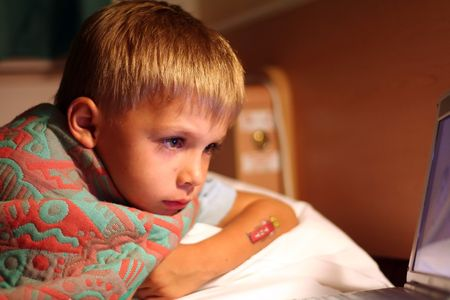 boy watching TV at night, from his bed photo