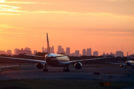 airplane before New York skyline, at departure, at sunset