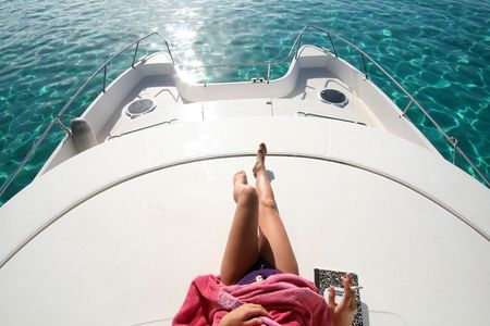 woman legs on the roof of a catamaran boat