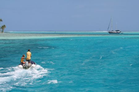 man and woman reaching the yacht witn an inflatable tender photo
