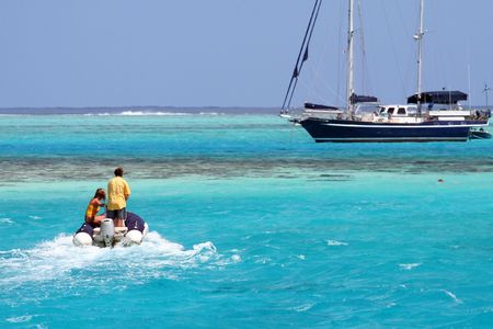 two persons on an inflatable tender, approaching the yacht photo
