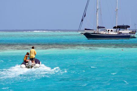 Zwei Personen auf einem aufblasbaren Tender, der Yacht nähernd Standard-Bild - 541687