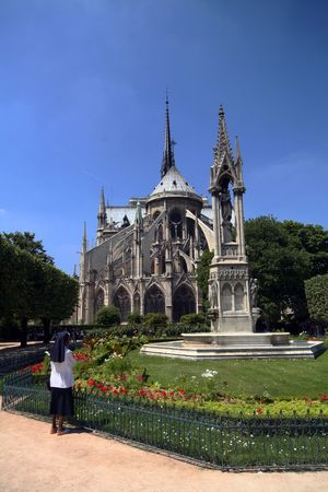 noun: religious woman praying in front of Notre Dame cathedral Stock Photo