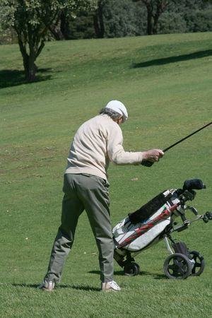 old golfer and his cart on the fairway Stock Photo