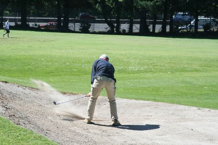chipping: golfer chipping out of a bunker