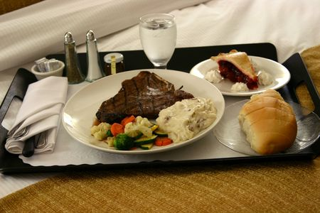 room service tray with steak and dessert