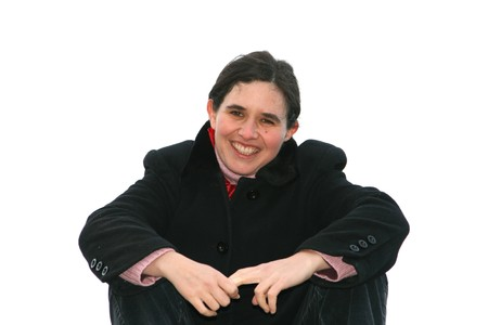 brune: woman seated with hands together on white background