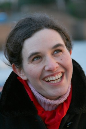 brune: woman in black coat and red scarf smiling