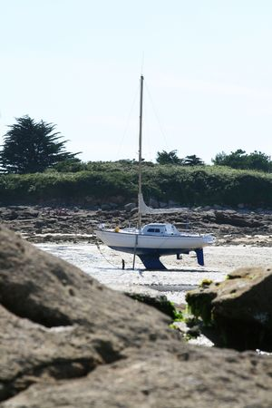 wreckage: boat on its keel ashore on sand