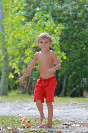 boy in red shorts running on the beach
