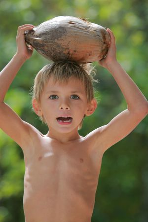 boy holding a coconut on his head