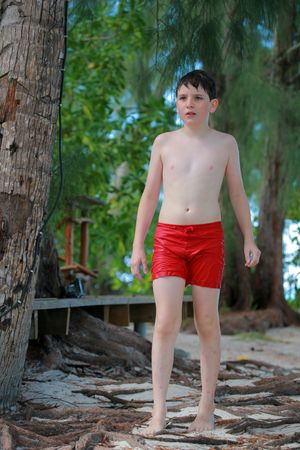 teenage boy walking on a tropical beach