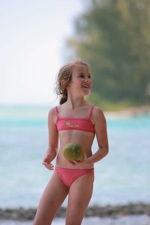 youngster  girl: girl playing with a coconut on the beach