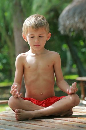 kid meditating with closed eyes photo