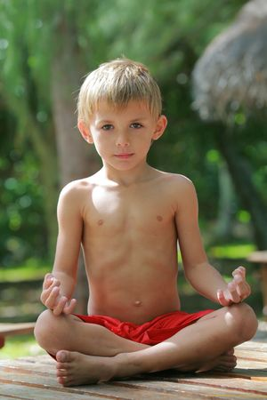 relaxing kid doing yoga lotus position Stock Photo