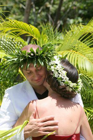 husband hugging wife in a tropical garden