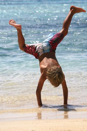 boy walking on his hands at beach photo