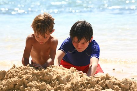 kids playind in the sand at the beach photo