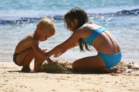 two kids playing in the sand at the beach