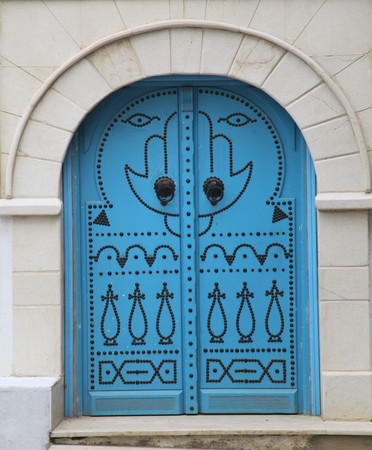 decorated blue arabic door with hand