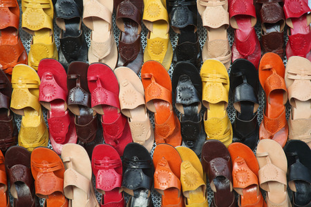 multicolor leather sandals on a market wall