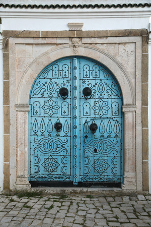 old blue door in paved street Standard-Bild