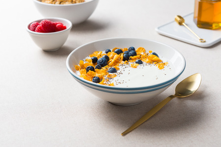 Healthy breakfast. Corn flakes with yogurt, blueberries and chia seeds. Served with maple syrup and raspberries on beige fabric background. Standard-Bild