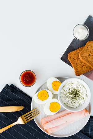 Breakfast, half boiled eggs, ham, fresh cheese sprinkled with dill, toast, horseradish sauce and sweet and sour sauce. Black kitchen cloth with golden cutlery. Flat lay on white background.