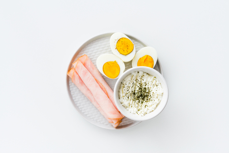 Breakfast, half boiled eggs, ham and fresh cheese sprinkled with dill. Top view, flat lay on white background. Stock Photo