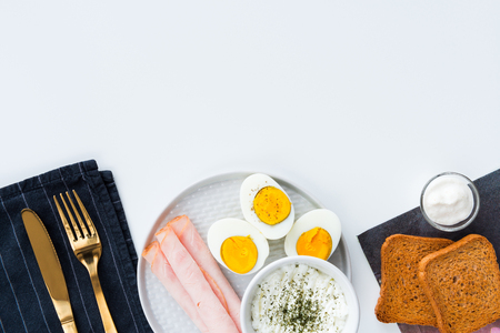 Breakfast, half boiled eggs, ham, fresh cheese sprinkled with dill, toast and horseradish sauce. Black kitchen cloth with golden cutlery. Flat lay on white background with copy space.