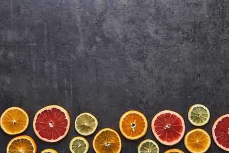 Flat lay of citrus fruits pattern of lemon, orange and grapefruit on black stone background. Copy space above. Top view. Stock fotó