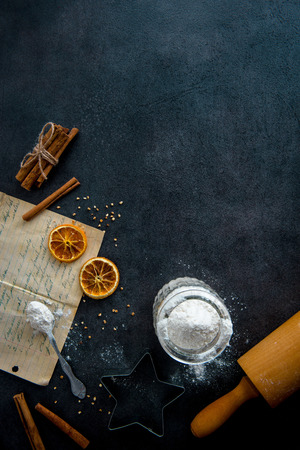 Food preparation. Old recipe, teaspoon, cookie cutter, rolling pin, mason jar with flour and ingredients (cinnamon sticks, dried orange slices) on dark modern table from above. Top view, copy space. 免版税图像