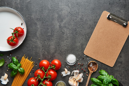 Food background for tasty Italian dishes with tomato. Various cooking ingredients with spoon and blank cardboard clipboard for menu or recipes. Top view with copy space.