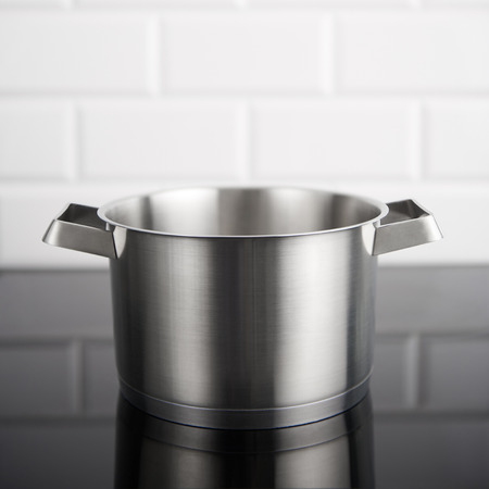 Stainless steel pot without cover on the induction stove with white metro tiles in the background. Square crop with copy space at the top.